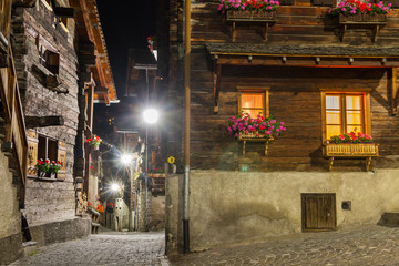 Beautiful traditional houses in the streets of the village Grimentz, Switzerland, canton Valais, municipality Anniviers, at night with geranium flowers on the balconies illuminated by streetlights