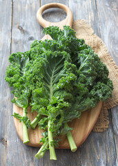 Fresh green curly kale leaves on a cutting board on a wooden table. selective focus. rustic style. healthy vegetarian food