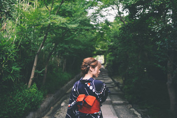 Rear view of young woman in traditional japanese clothing on treelined path