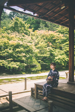 Young woman in traditional Japanese clothing sitting on wooden porch