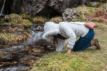 Woman with white puffy jacket and hiking shoes and scarf drinking fresh pure water from the stream at Glencoe Scottish Highlands