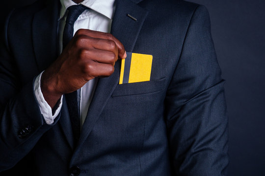 young successful businessman man in a stylish black classic suit and in cool glasses holding a yellow plastic credit card in the studio on a dark background. shopping concept