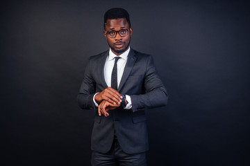 handsome black successful and clever american student with glasses in the University in dark suit. Studio fashion shot isolated on black background.