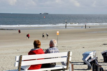 Ebbe an der Nordsee / ideal für lange entspannte Strandspaziergänge. Ein älteres Paar verweilt auf einer Bank oben an der Strandpromenade mit Blick auf das weite Meer mit Frachter