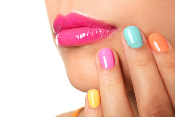 Beautiful young woman with colorful manicure on white background, closeup