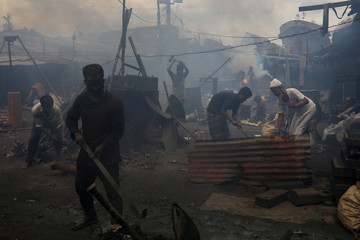 People work in a polluted environment at a dockyard in Dhaka