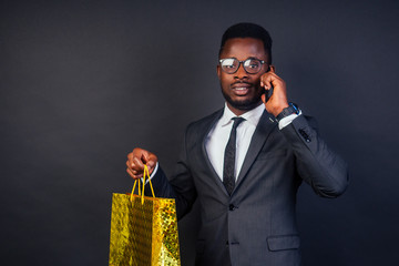 black Friday sale idea. African American man using mobile phone , happy dark skinned businessman holding a shopping bag