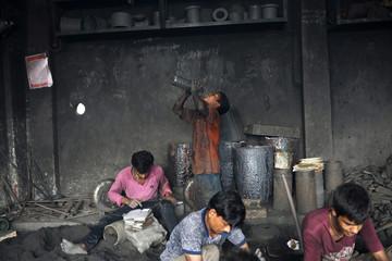 Shakil, a child worker drinks water as he takes a break at a dockyard in Dhaka