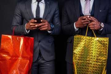 African american male business partners holding shopping bags on a black background in the studio.black Friday sale seasonal concept