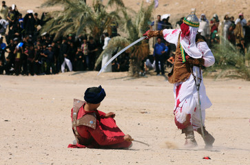 Local actors dressed as ancient warriors re-enact a scene from the 7th century battle of Karbala to commemorate Ashura in Najaf