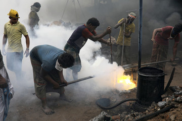 Workers melt metal scrap to make propeller for ferry at a dockyard in Dhaka