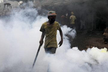 A man works in a polluted smoky environment of a dockyard in Dhaka