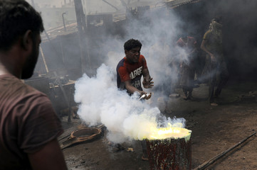 A man pours chemical powder into melted metal scrap to make a propeller for ferry at a dockyard in Dhaka