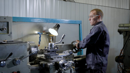 Industrial plant worker working at the lathe machine.