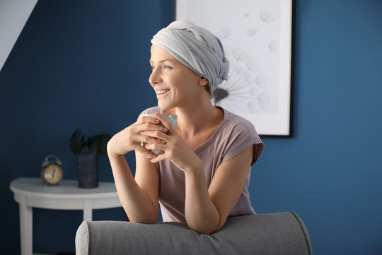 Happy woman after chemotherapy drinking tea at home