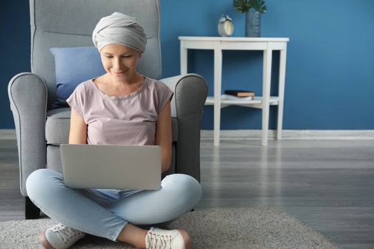 Woman after chemotherapy using laptop at home