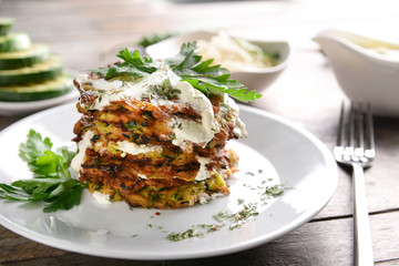 Plate with tasty zucchini pancakes on wooden table, closeup