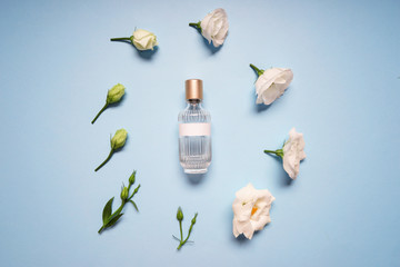 Beautiful composition with bottle of perfume and flowers on color background