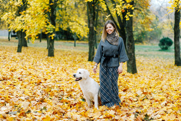 woman hugging her dog in the park in autumn