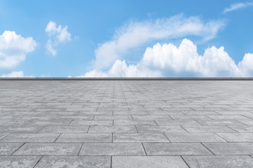 Empty stone floor under blue sky and white clouds