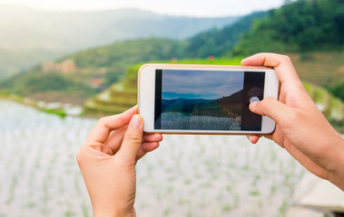 Girl capturing rice terrace scenery with a phone