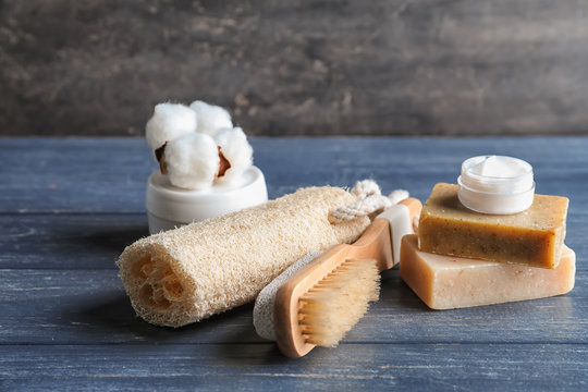 Bath products with loofah and brush on dark wooden table