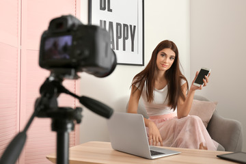 Young female blogger recording video indoors