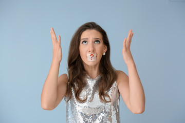 Emotional woman with taped mouth on color background. Diet concept