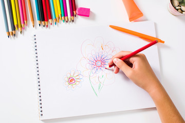 Girl drawing a colorful flower first person