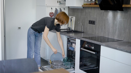 Woman loading dirty dishes into dishwashing machine