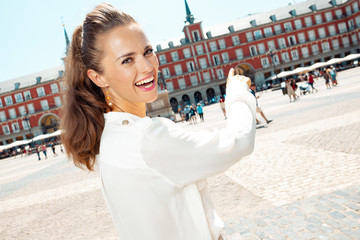 woman at Plaza Mayor in Madrid, Spain pointing at something