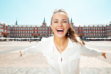 smiling tourist woman at Plaza Mayor in Madrid, Spain rejoicing