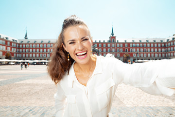 happy young woman at Plaza Mayor in Madrid, Spain taking selfie