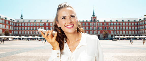 smiling traveller woman listening to audio guide on smartphone