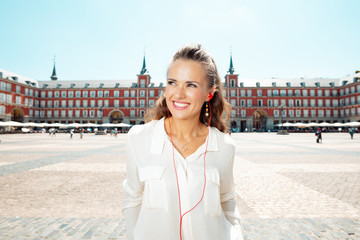 smiling woman looking into distance and listening to audio guide