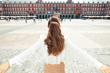 traveller woman at Plaza Mayor in Madrid, Spain rejoicing
