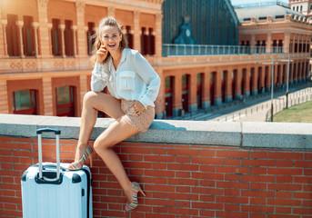 smiling elegant tourist woman while sitting on parapet