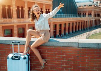 happy stylish tourist woman handwaving while sitting on parapet