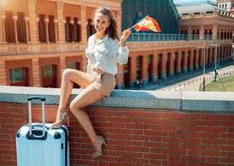 smiling traveller woman with Spain flag sitting on parapet