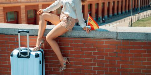 smiling elegant woman with Spain flag sitting on parapet