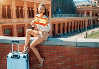 smiling traveller woman showing Spain flag sitting on parapet