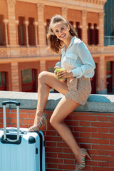 smiling traveller woman with green smoothie sitting on parapet
