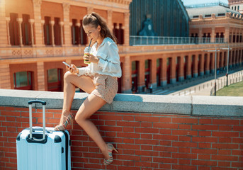 traveller woman with green smoothie with smartphone using applications