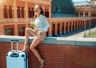 cheerful traveller woman with green smoothie sitting on parapet