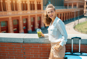 smiling trendy woman with trolley bag and green smoothie