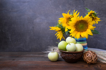 Autumn harvest, natural products, Greeting card concept. Still life with beautiful sunflower flower, green apples in clay brown bowl, wheat spikelets on wooden rustic background.