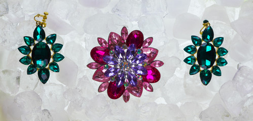 valuable brooch with precious stones on ice cubes