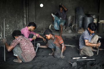 Workers including children work at a dockyard in Dhaka