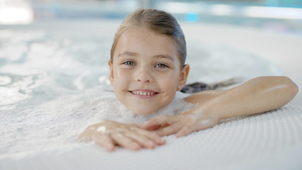 pretty little girl with wet hair is sitting alone in hydromassage bath in a water park, looking to camera