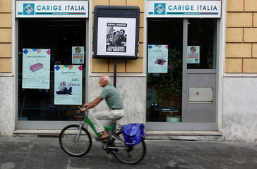 A man rides a bicycle past a Carige bank in Rome